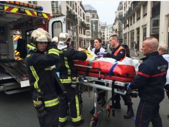 Photo of Emergency workers loading one the injured employees of Charlie Heb Magazine into an ambulance after jihad massacare in France